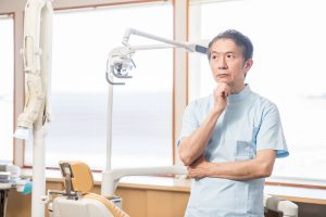photo shows a dentist contemplating dental website design costs and pricing